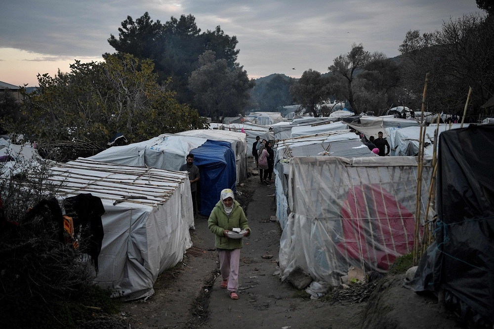 Migrants walk in the overcrowded makeshift migrant camp on the island of Chios December 10, 2019. — AFP pic