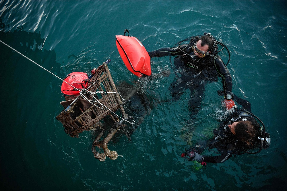 Divers volunteering for the Aegean Rebreath Greek organisation retrieve rusted shopping carts from the sea in the port of the Ionian island of Zakynthos November 23, 2019. — AFP pic