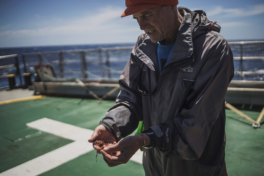 Retired Marine Biologist Professor Robert Anderson examines algae retrieved from a ghost fishing device onboard the Greenpeace vessel Artic Sunrise at the end of an exploration of Vema Sea Mount October 31, 2019. — AFP pic