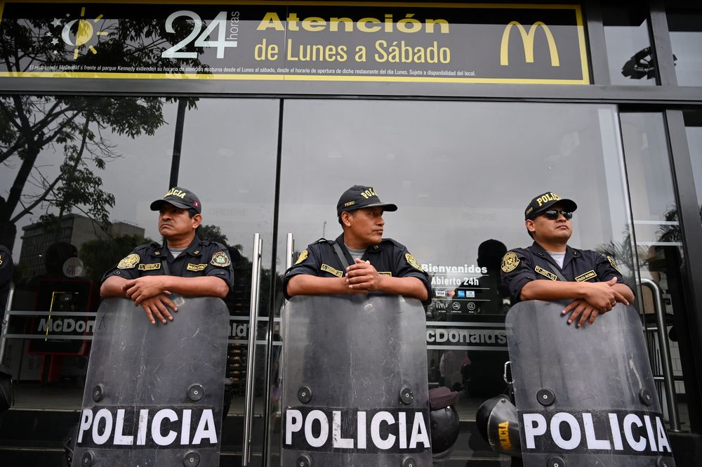 Police stand guard outside a closed McDonald's restaurant, during a protest after the deaths of two teenaged employees, in Lima, Peru December 21, 2019. — Reuters pic
