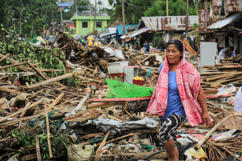 A resident walks past debris from their destroyed houses after Typhoon Kammuri hit the city of Sorsogon, south of of Manila December 3, 2019. — AFP pic