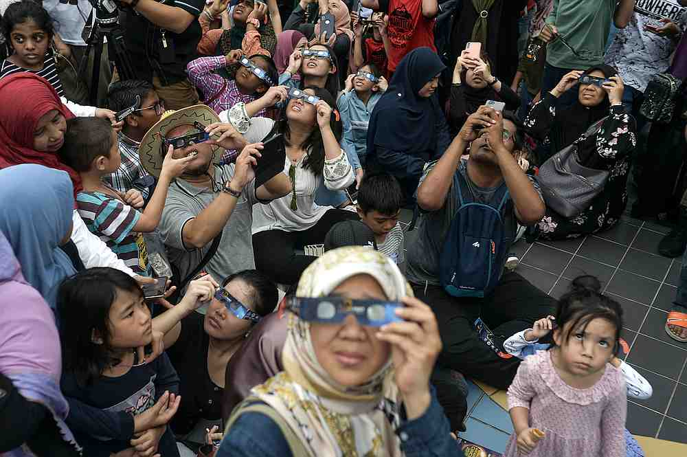 Visitors use the solar filter glasses provided by the National Planetarium to view the annular solar eclipse in the grounds of the National Planetarium in Kuala Lumpur December 26, 2019. — Picture by Shafwan Zaidon