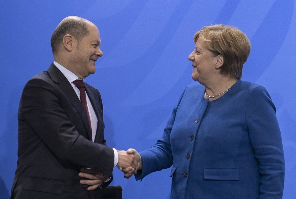 German Chancellor Angela Merkel and German Finance Minister and Vice-Chancellor Olaf Scholz shake hands after a press conference on December 16, 2019 at the Chancellery in Berlin. — AFP pic