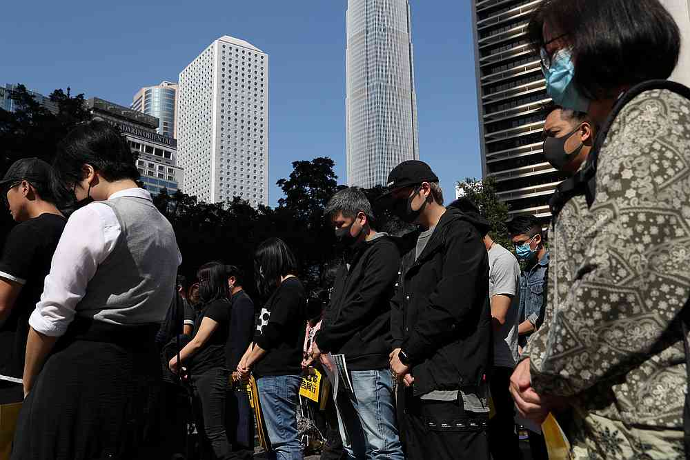 Anti-government demonstrators stand still during a moment of silence as people gather for a lunchtime protest at Chater Garden in Hong Kong December 2, 2019. — Reuters pic