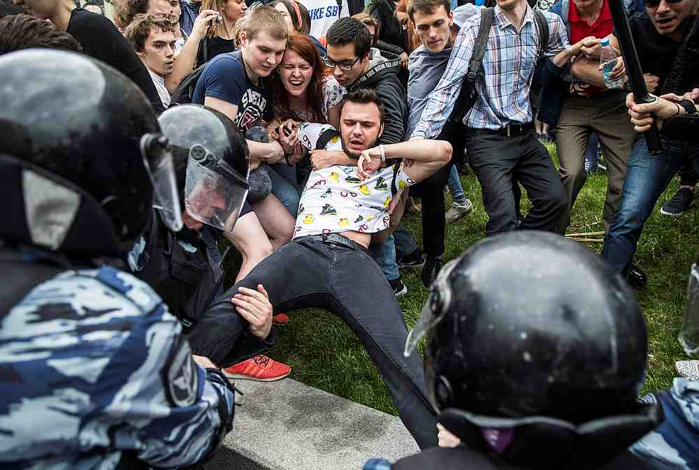 Russian law enforcement officers attempt to detain Ruslan Shaveddinov, a project manager at Anti-Corruption Foundation, during a rally in Moscow June 12, 2017. — Reuters pic