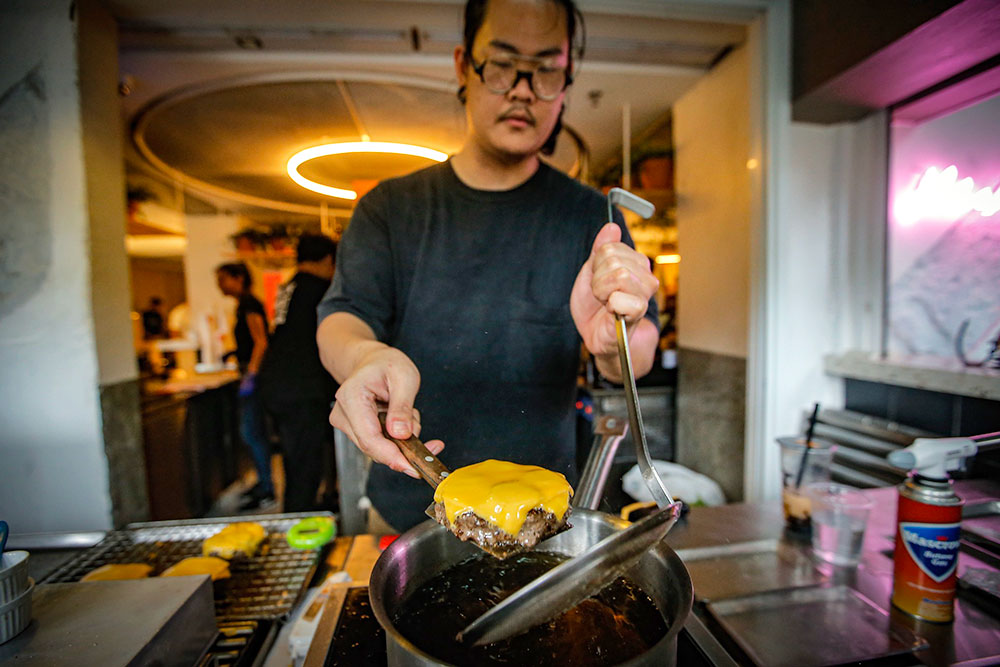 Once the patty is ready, the cheese is bathed in hot oil to melt it.