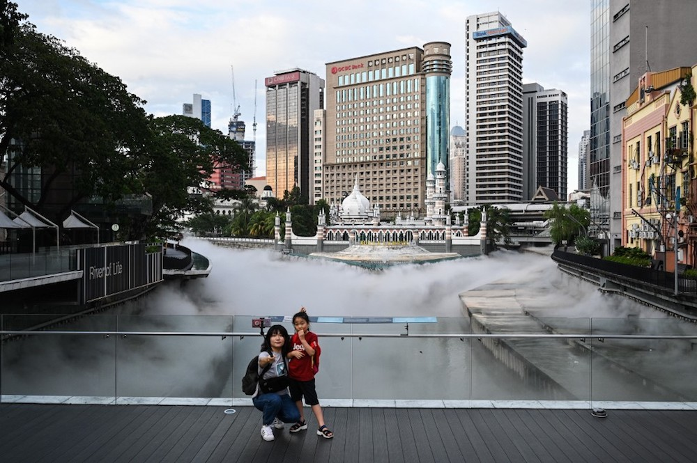 File picture shows tourists taking pictures at the River of Life waterfront, covered with mist effects, where the Gombak River joins the Klang River near Masjid Jamek in Kuala Lumpur January 6, 2020. — AFP pic