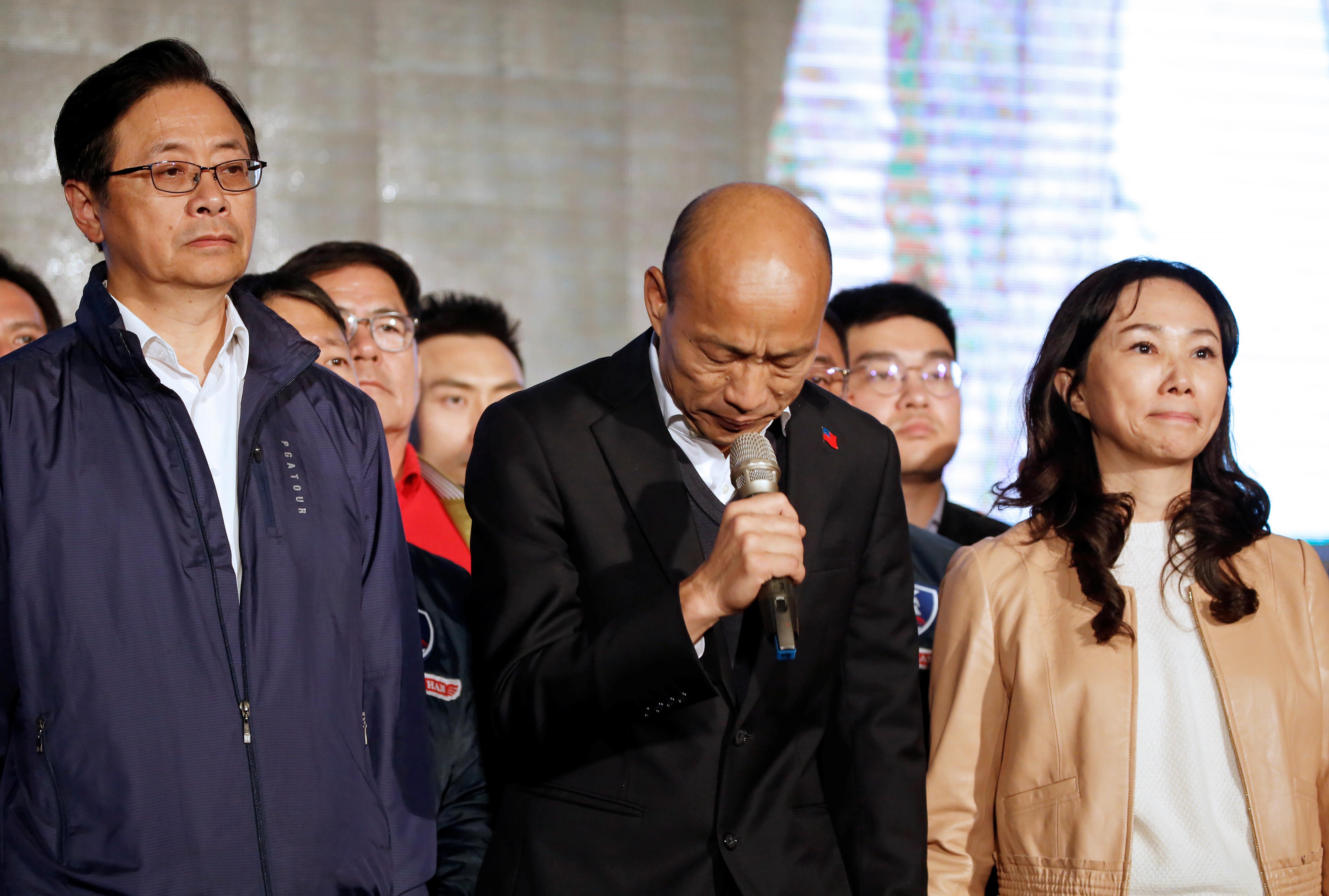 国民党总统候选人韩国瑜(中)、副总统候选人张善政(左)和韩妻李佳芬周六晚间现身高雄市党部外,正式发表败选感言,感谢众人一路相挺。-路透社-
