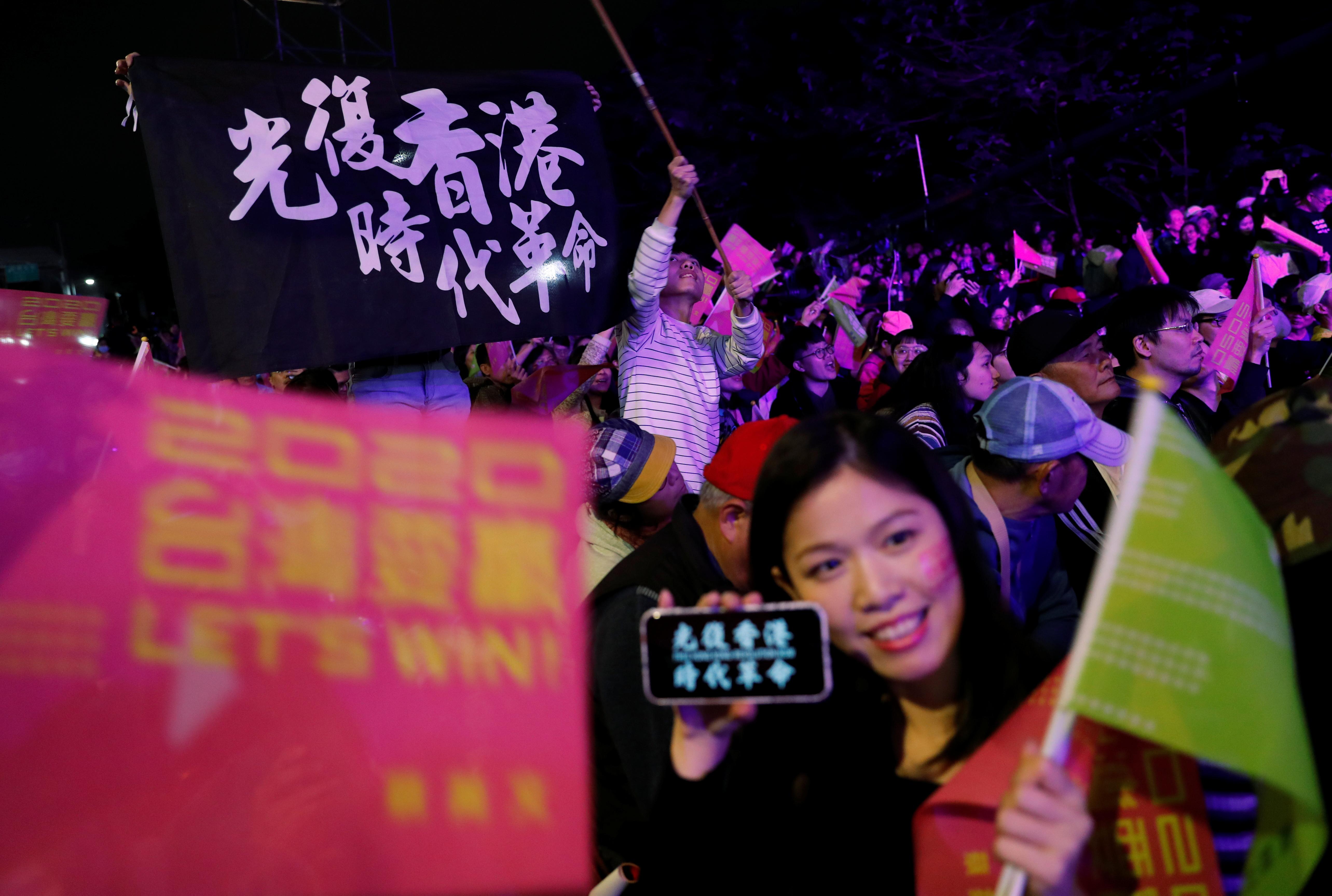 """日本媒体普遍认为,香港""""反送中""""运动是蔡英文胜选的因素。周六晚在民进党总部外,支持者高举香港反送中口号的旗帜。-路透社-"""