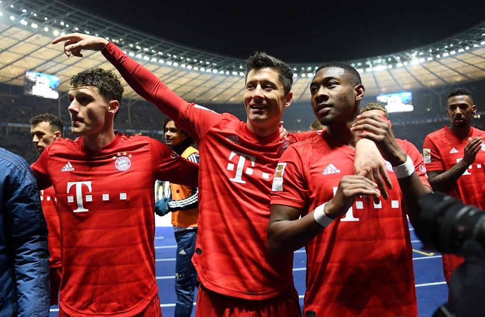 拜仁慕尼黑一线队球员莱万多夫斯基、阿拉巴和帕瓦尔在场上庆祝进球,他们和其他队员将在周一恢复训练。-路透社-