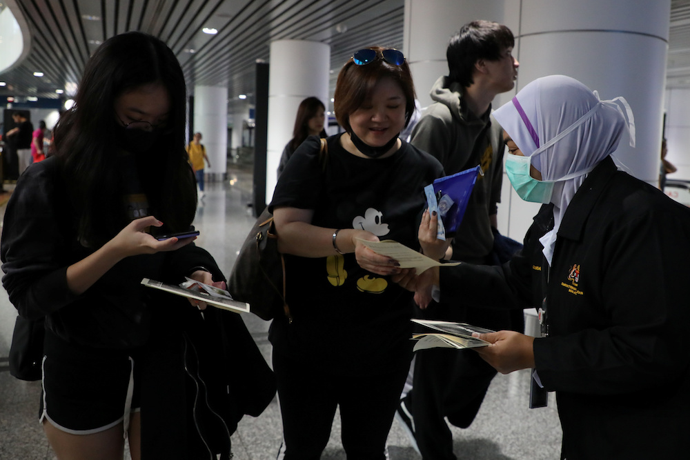 A Malaysian health quarantine officer distributes leaflets about the Wuhan Pneumonia to passengers at Kuala Lumpur International Airport in Sepang January 21, 2020. — Reuters pic