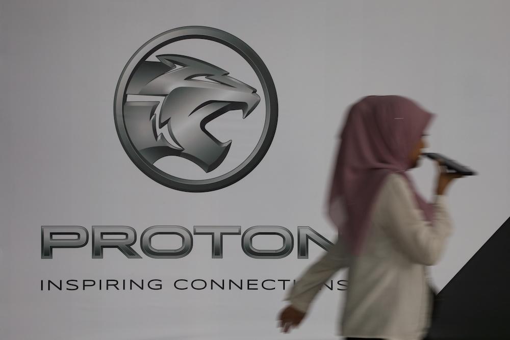 A woman walks past a logo of Proton at its headquarters in Subang Jaya, January 20, 2020. — Reuters pic