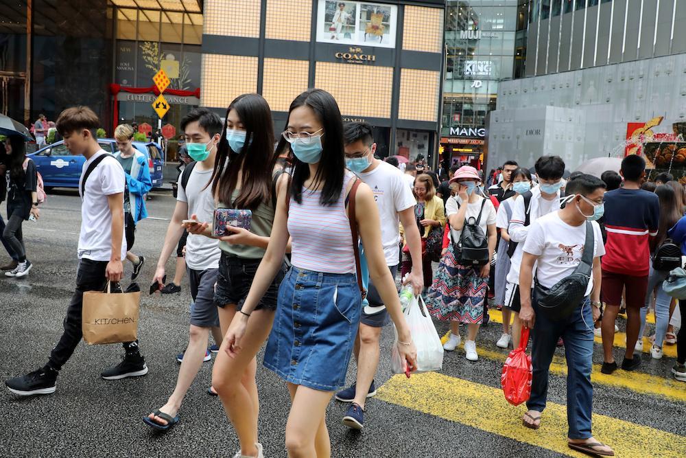 Tourists wearing masks cross a street outside a shopping mall in Kuala Lumpur January 29, 2020. — Reuters pic