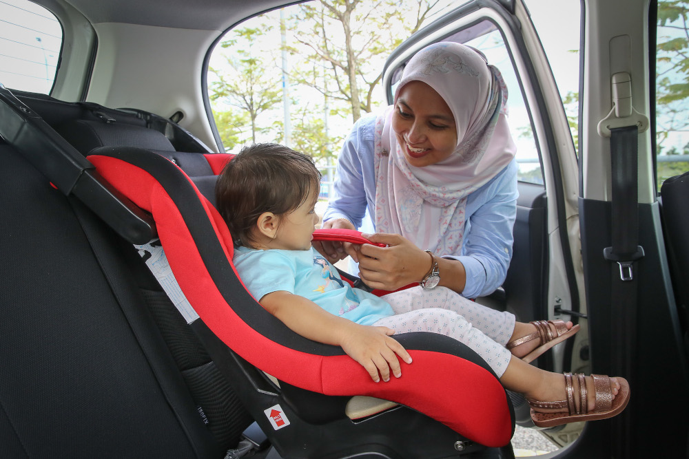 A mother, Anis Ilyani Azhar, testing out a child seat with her daughter Ameena Yasmin in Shah Alam January 4, 2020. — Picture by Yusof Mat Isa