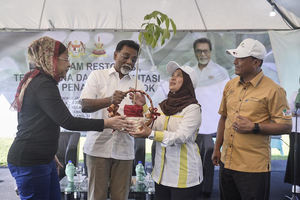 Datuk Dr Xavier Jayakumar (centre) gives a sapling to Klang Municipal Council secretary Elya Marini Darmin during the launch of the Restoration, Reclamation and Rehabilitation Through Tree Planting Programme in Klang January 5, 2020. — Picture by Miera Zulyana