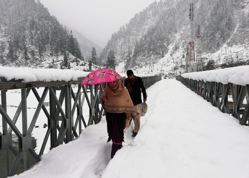 People walk on a snow-covered bridge after a heavy snowfall in Neelum Valley near the Line of Control (LoC), Pakistan, January 15, 2020. —Reuters pic