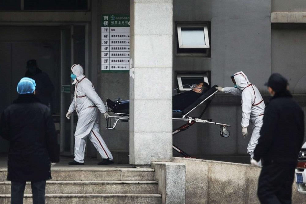 深圳出现新型冠状病毒疑似个案。深圳第三人民医院在周六下午,两名穿着全套白色防护衣及口罩的职员协助收治一名患者,并将他送往感染病楼的电梯。-法新社-