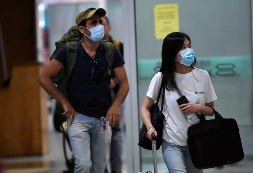 Tourists wear masks upon arrival at the Kota Kinabalu International Airport following the coronavirus infection January 24, 2020. — Bernama pic