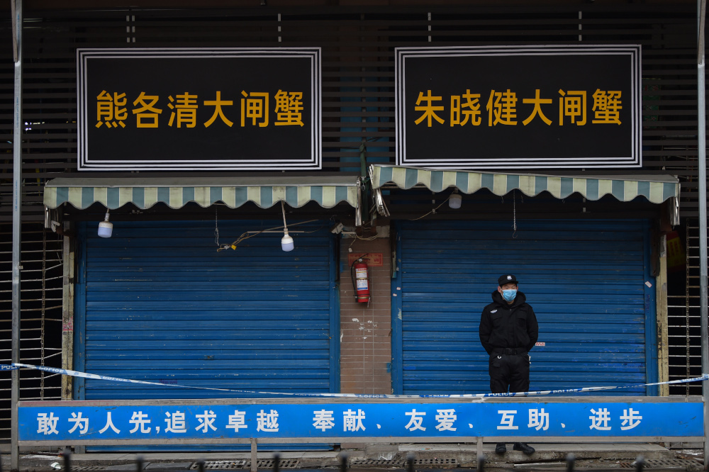 A security guard stands outside the Huanan Seafood Wholesale Market where the coronavirus was detected in Wuhan January 24, 2020. — AFP pic