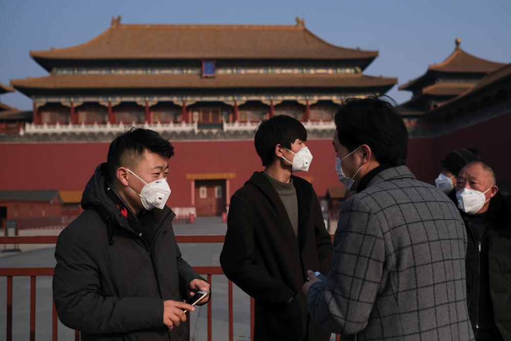 People wearing protective masks stand outside the main entrance of the Forbidden City where a notice is seen saying that the place is closed to visitors for the safety concern following the outbreak of a new coronavirus, in Beijing, China January 25, 2020