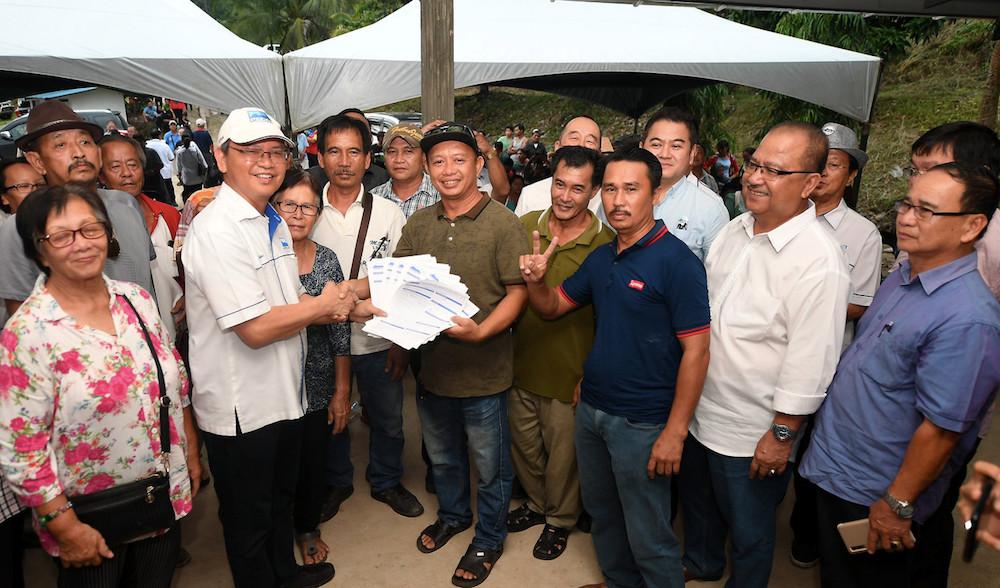 Upko president Datuk Wilfred Madius Tangau (white cap) receives new party membership applications during a party gathering in Kampung Kinolonsodon, Kimanis January 16, 2020. — Bernama pic