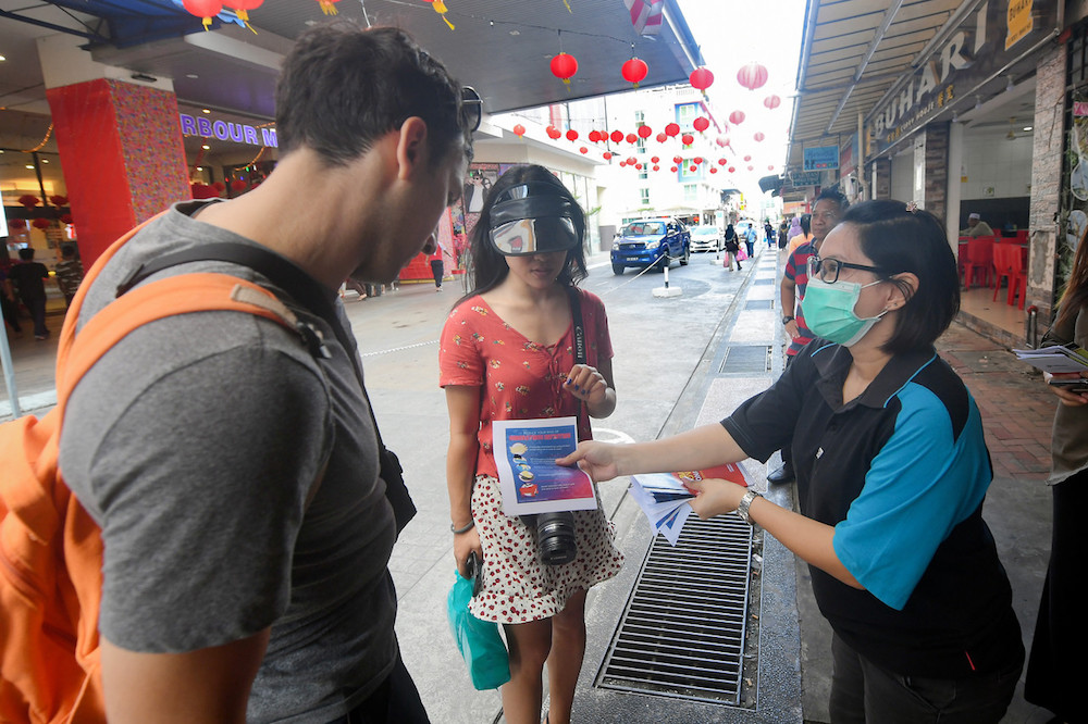 A Sandakan Information Department staff distributes leaflets on the 2019 novel coronavirus infection to tourists in Sandakan January 30, 2020. Sabah Sports Board (SSB) chairman Dr KH Tan said the board is allowing the use of the Sandakan Sports Complex Hostel as a Covid-19 treatment centre following the increase in the number of positive cases in the district. — Bernama pic