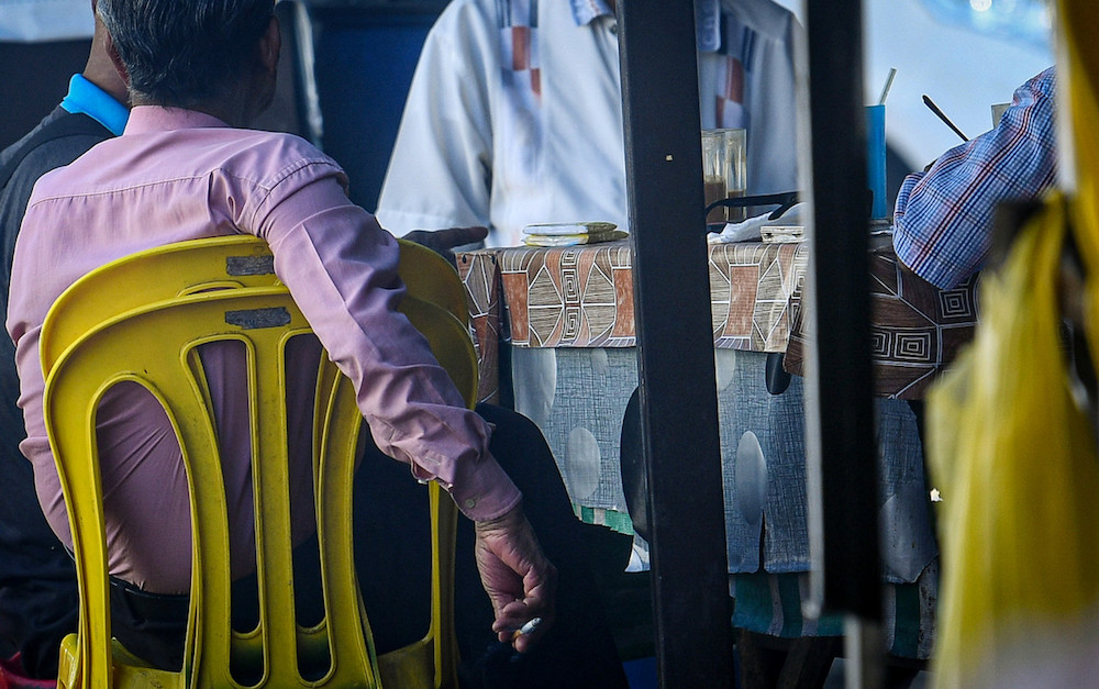 A man attempts to conceal his cigarette as health officers approach his table during an inspection at an eatery in Medan Selera Jalan Raja Muda Abdul Aziz in Kuala Lumpur January 1, 2020. — Bernama pic