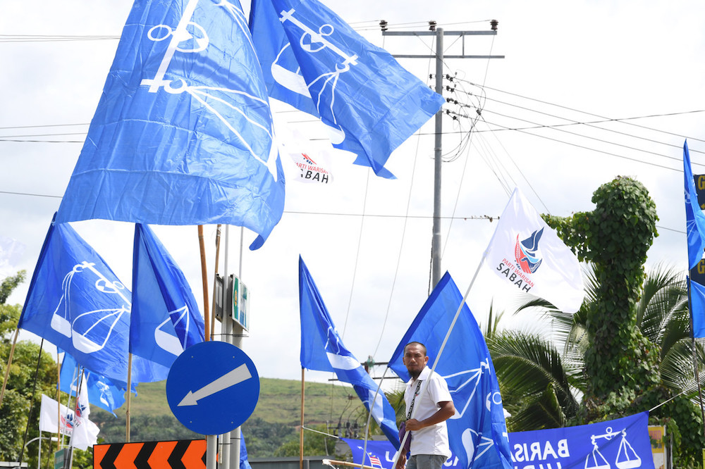 A man holds a Warisan flag in front of a sea of Barisan Nasional flags in Membakut January 5, 2020, ahead of the Kimanis by-election on January 18. — Bernama pic