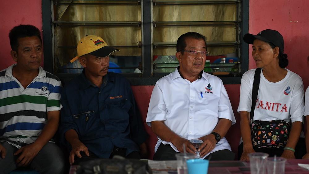 Warisan candidate Datuk Karim Bujang speaks to people at their home in Kampung Kelatuan, Papar January 8, 2020. — Bernama pic
