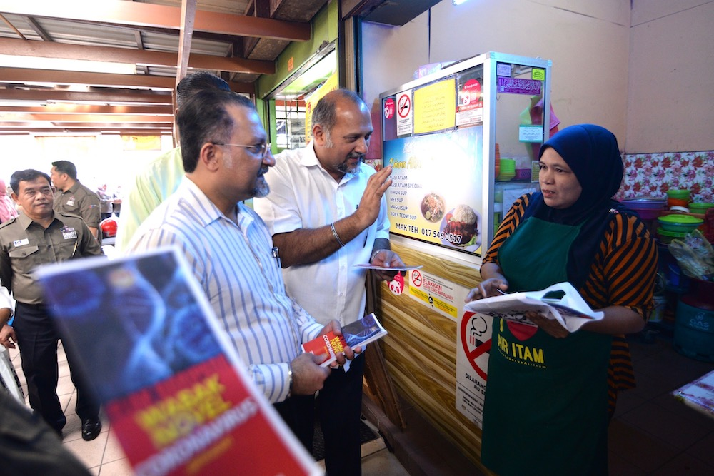 Communication and Multimedia Minister Gobind Singh Deo talking to a stall owner at the Lorong Kulit hawker centre in Penang January 30, 2020. — Picture by Steven Ooi KE