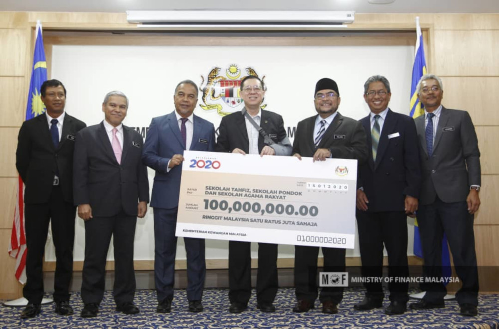 Finance Minister Lim Guan Eng hands over the RM100 million allocation to Minister in the Prime Minister's Department Datuk Seri Mujahid Yusof at the Finance Ministry in Putrajaya January 15, 2020. — Picture from Twitter/Ministry of Finance