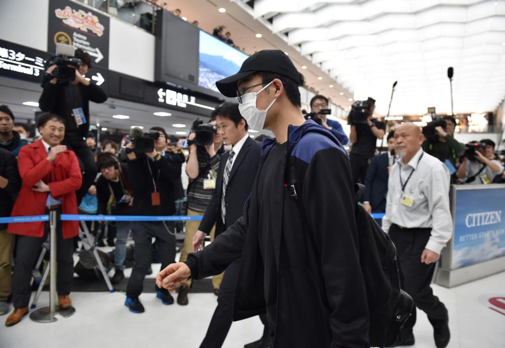 Top-ranked Japanese badminton player Kento Momota arrives at Narita Airport in Chiba prefecture January 15, 2020. — AFP pic
