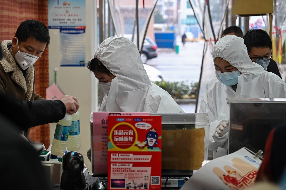Pharmacy workers wearing protective clothes and masks serve customers in Wuhan January 25, 2020. — AFP pic
