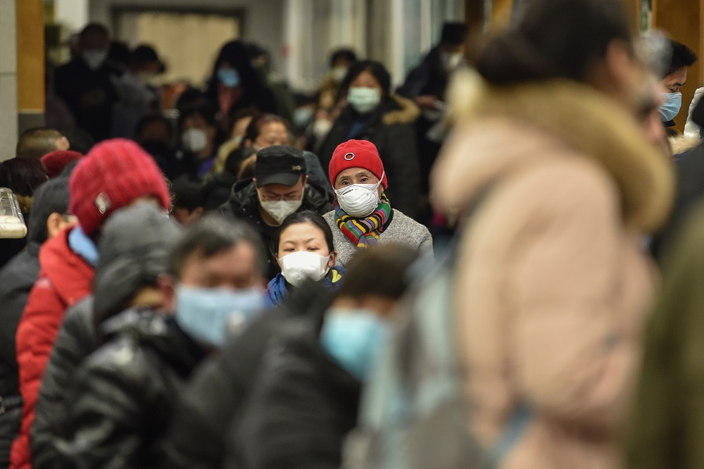 People wearing facemasks to help stop the spread of a deadly virus which began in the city, wait at Wuhan Red Cross Hospital in Wuhan January 24, 2020. — AFP pic