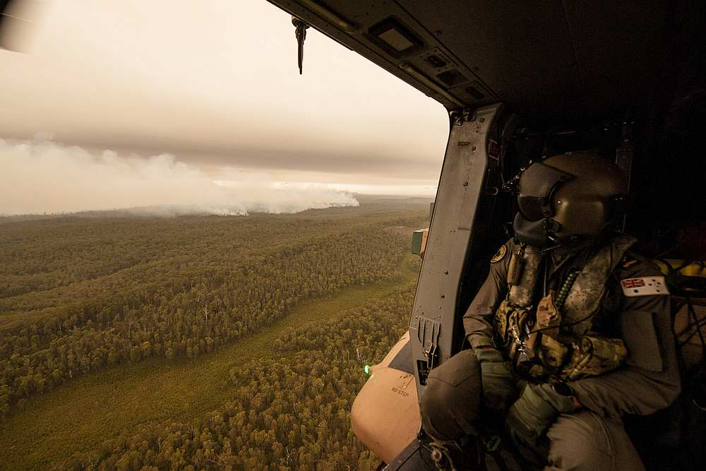 A Royal Australian Navy MRH-90 helicopter crew member, observes the fires on approach to Cann River in Gippsland, Victoria, Australia January 5, 2020. — Private Michael Currie/Australian Department of Defence handout via Reuters