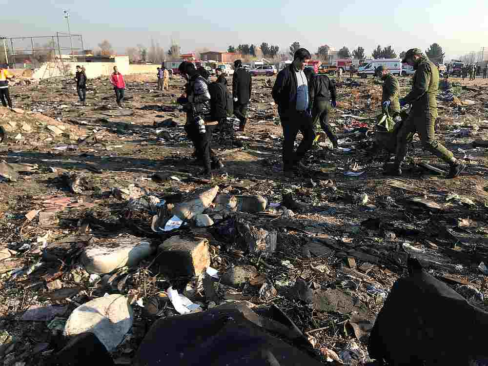Rescue team members with people check the debris from a plane crash belonging to Ukraine International Airlines after take-off from Iran's Imam Khomeini airport, on the outskirts of Tehran, Iran January 8, 2020. — Wana pic via Reuters