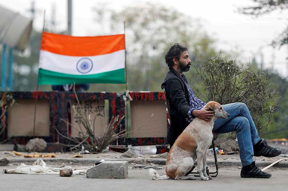 A man sits with a dog on a road blocked by demonstrators to protest against a new citizenship law, in New Delhi, India January 6, 2020. — Reuters pic