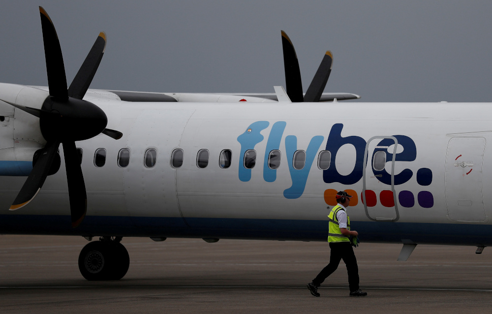 An airport worker examines a Flybe aircraft before it takes off from Liverpool John Lennon Airport in Liverpool May 19, 2016. — Reuters pic