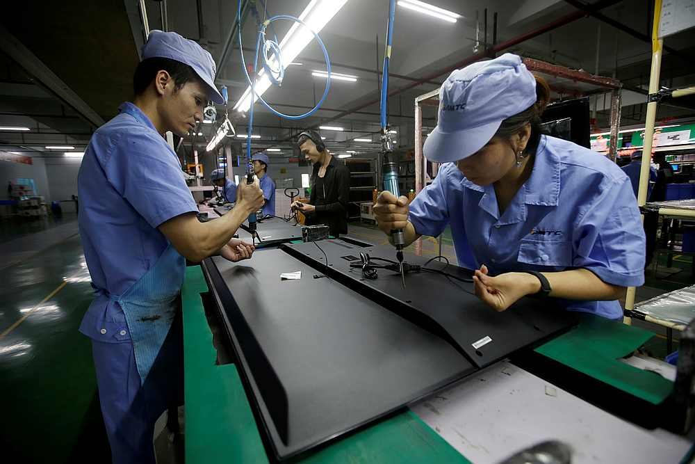 Employees work on the production line of a television factory under Zhaochi Group in Shenzhen, China August 8, 2019. — Reuters pic