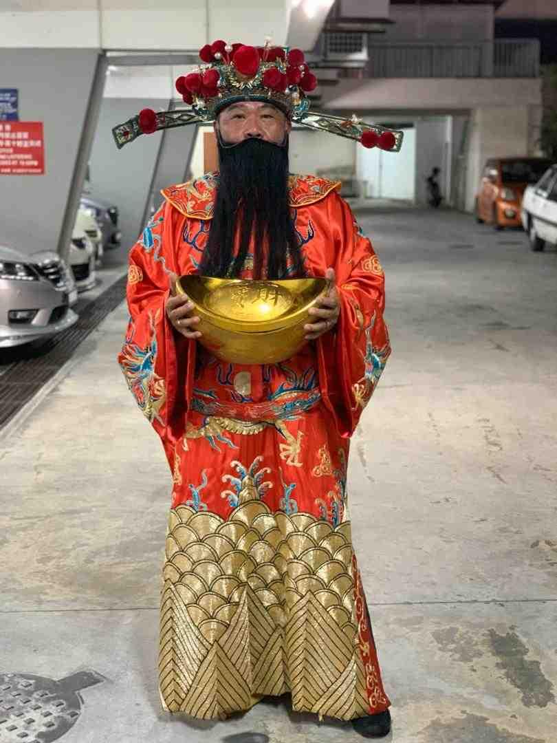 陈荣达需要花30分钟来穿财神爷的服装。-Steven Chan摄-