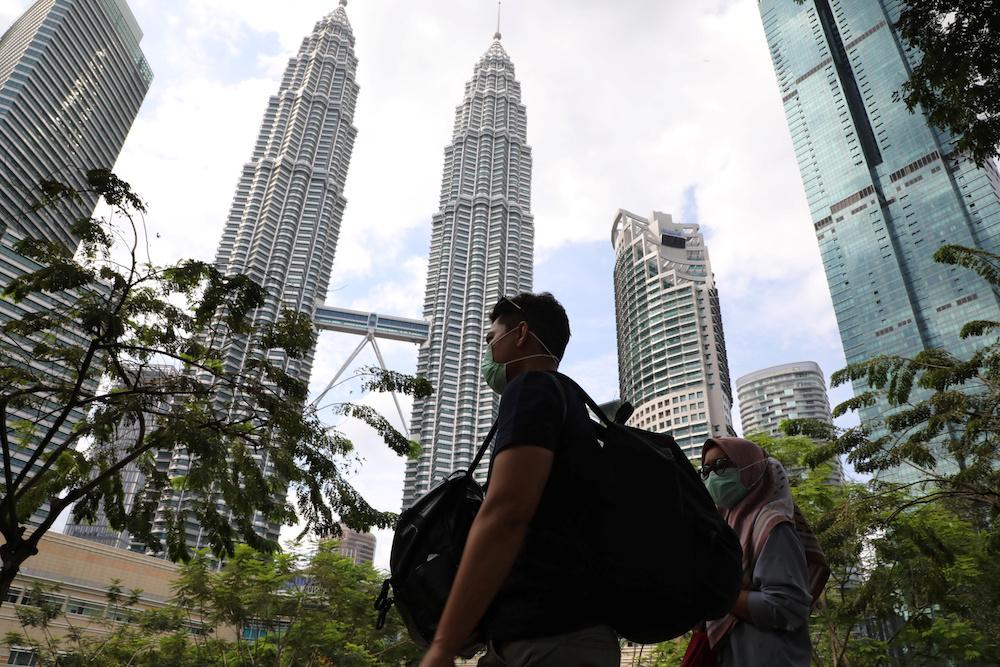 People wearing masks pass by Petronas Twin Towers in Kuala Lumpur January 31, 2020. — Reuters pic