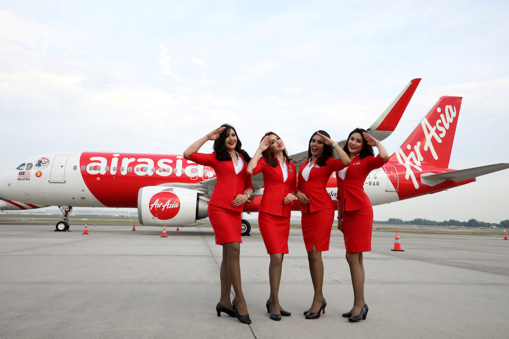 AirAsia crew members pose for a photograph in front of an Airbus A320-200 plane at Kuala Lumpur International Airport in Sepang July 22, 2019. — Reuters pic