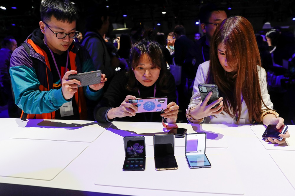 Attendees take photographs of the new Samsung Galaxy Z Flip foldable smartphone during Samsung Galaxy Unpacked 2020 in San Francisco February 11, 2020. — Reuters pic