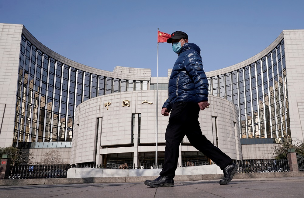 A man wearing a mask walks past the headquarters of the People's Bank of China, the central bank, in Beijing as the country is hit by an outbreak of the new coronavirus, February 3, 2020. — Reuters pic