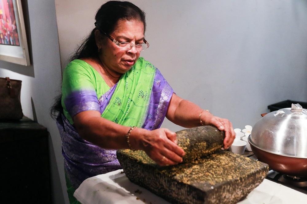 Parvathy using the traditional Sri Lankan grinding stone to make a sambal paste. — Picture by Ahmad Zamzahuri
