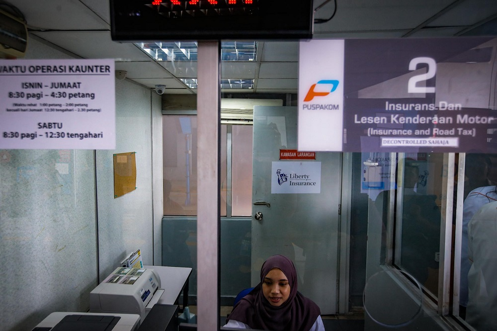 A staff is seen at one of the service counters located at the Wangsa Maju Puspakom branch in Kuala Lumpur February 7, 2020. — Picture by Hari Anggara