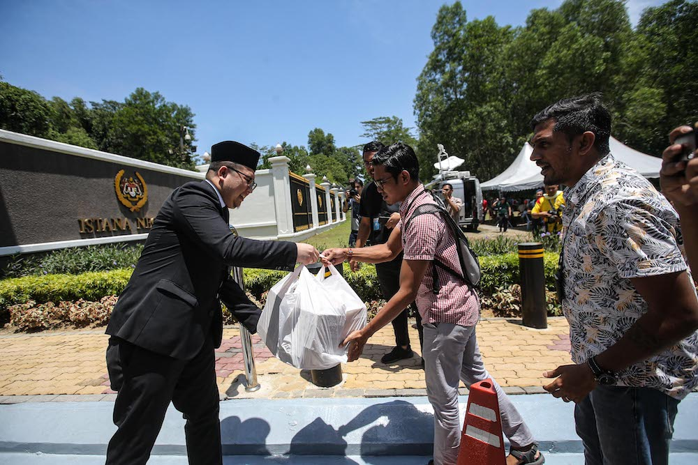 A palace representative distributes food and drinks to media personnel camped outside Istana Negara, February 29, 2020. A special fund to facilitate journalists in carrying out their duties during the Covid-19 outbreak was launched today. — Picture by Hari Anggara