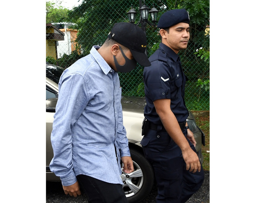 Nabil Hariz Jefridin (left) is led to the Magistrate's Court in Rembau February 18, 2020. — Bernama pic