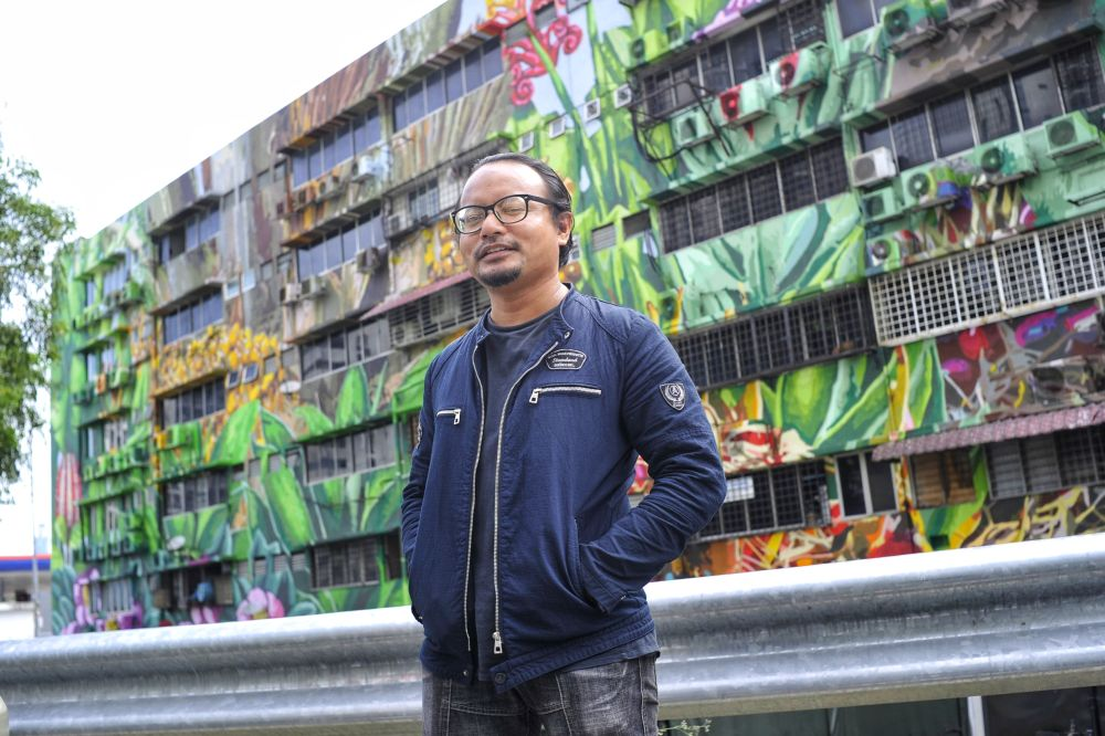 Artist Fadzlan Rizan Johani strikes a pose with his mural masterpiece in front of the Indah UPC building along Jalan Klang Lama, February 12, 2020. — Picture by Shafwan Zaidon