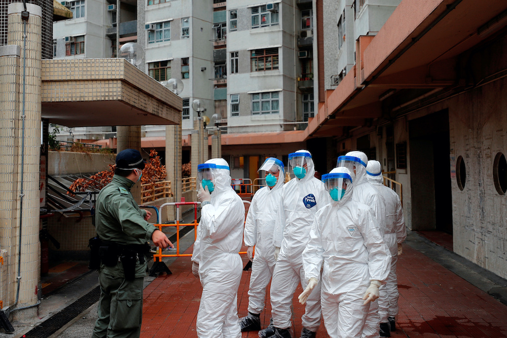 Police in protective gear wait to evacuate residents from a public housing building, following the outbreak of the novel coronavirus, in Hong Kong, China February 11, 2020. — Reuters pic